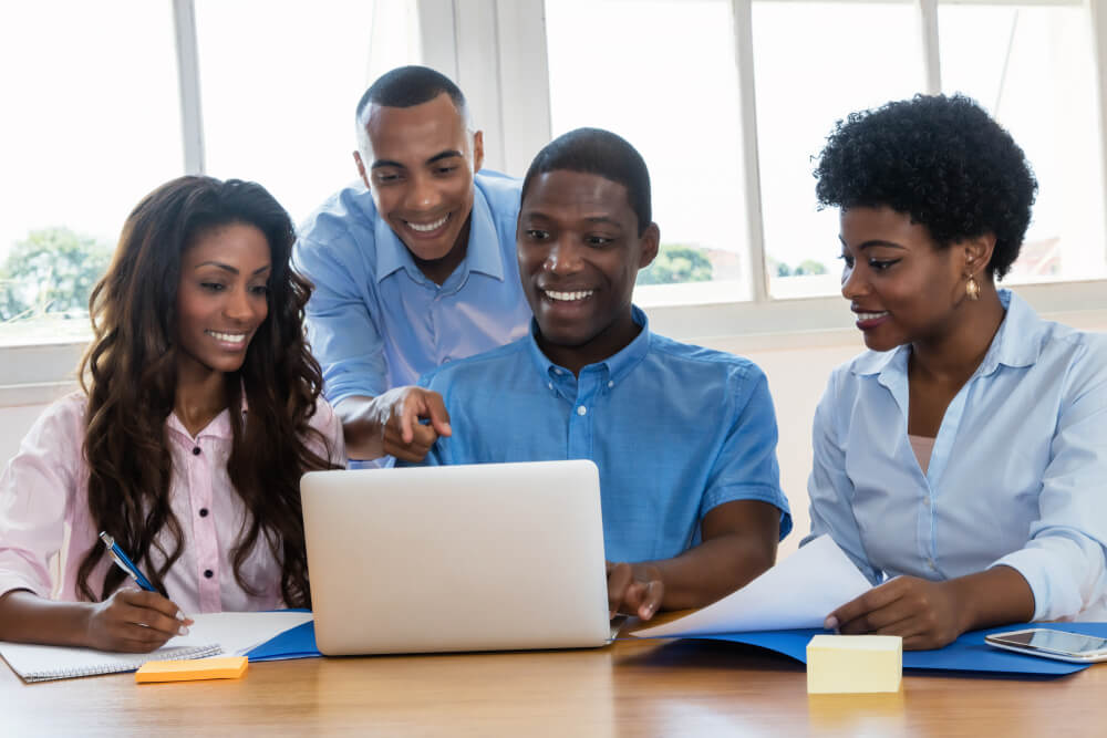 A group of people staring excitedly at a laptop screen